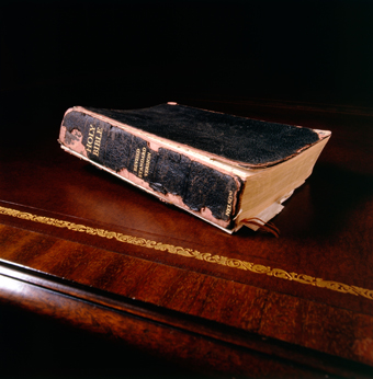 Still life study of a Holy Bible on an antique leather top desk