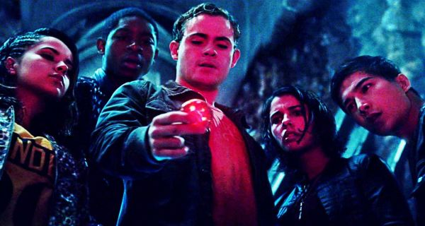 The Power Rangers cast, slightly damp, looking at a glowing red object that casts their faces in red. From left to right we have the Yellow Ranger, the Blue Ranger, the Red Ranger (who is holding the glowing red coin), the Pink Ranger and the Black Ranger. They all look on with expressions of surprise. This is a still from the 2017 Power Rangers movie.
