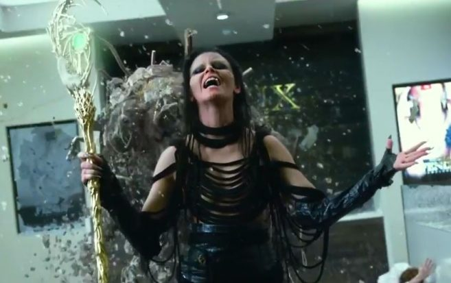 Rita Repulsa (played by Elizabeth Banks) has her arms up while holding a staff made of gold. Her face is exultant and there is a lot of golden debris flying around her. This is a still from the 2017 Power Rangers film.