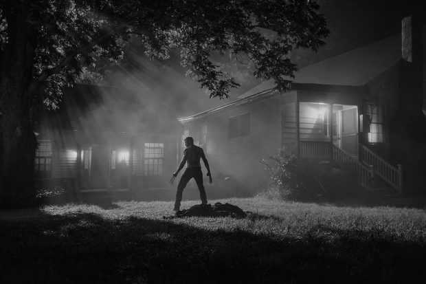 A long shot from the movie Logan, in black and white. There is a man standing over what looks to be a body, silhouetted in the darkness.