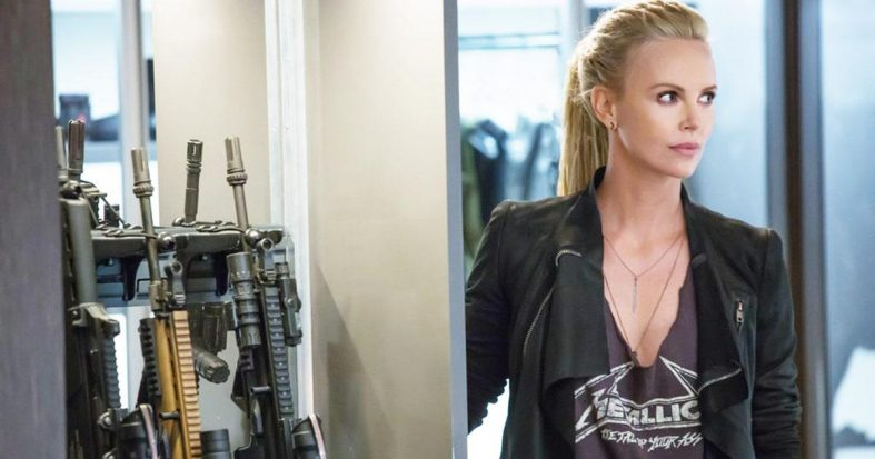Charlize Theron (as Cipher) standing on the right. To her left is a collection of rifles and other guns. She is wearing a Metallica t-shirt with a deep v cut into it and has white dreads.
