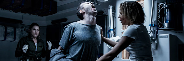 a man in a grey shirt, arches his back in clear agony while a woman stands in front of him and a clearly upset woman stands behind him. THis is a still from the film Alien Covenant