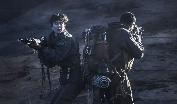 A woman and a man, back to back with their guns out. This is a still from the film Alien: Covenant