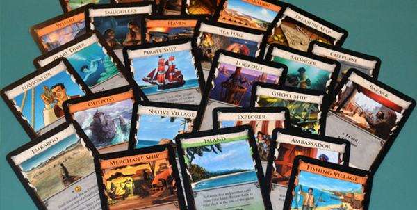 A pile of cards spread across a table, from the deck building game Dominion