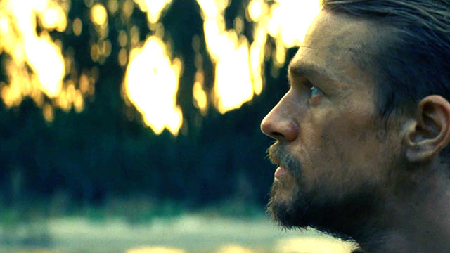 Charlie Hunnam (as Percy Fawcett) looking out over a verdant green background. This is a still from the film the Lost CIty of Z