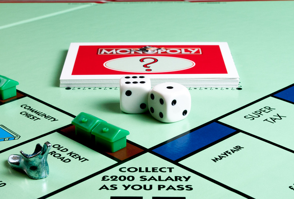 """A close up shot of dice and cards and the corner of the Monopoly board tha treads """"Collect $200 Salary as You Pass"""""""