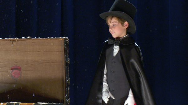Jacob Tremblay as Peter, dressed up as a pint sized magician in black top hat and cape, standing next to an open trunk on the floor on a well lit stage. This is a still from the movie Book of Henry