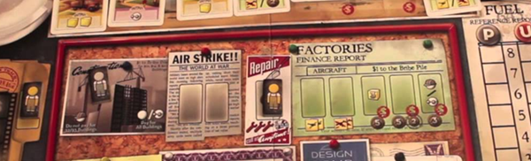 "A close up look at the cards and board from the game the Manhattan Project. The board has a vintage field and the words ""air strike"" ""factories"" and ""repair"" are easily readable."