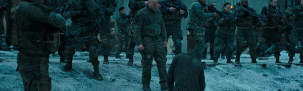Caesar, the ape, sitting on his knees in the snow in a supine position to a row of soldiers. This is a still from the film War for the Planet of the Apes.