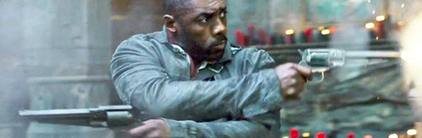 Idris Elba shooting two hanguns in opposite direction with his arms crossed. This is a still from the movie the Dark Tower.