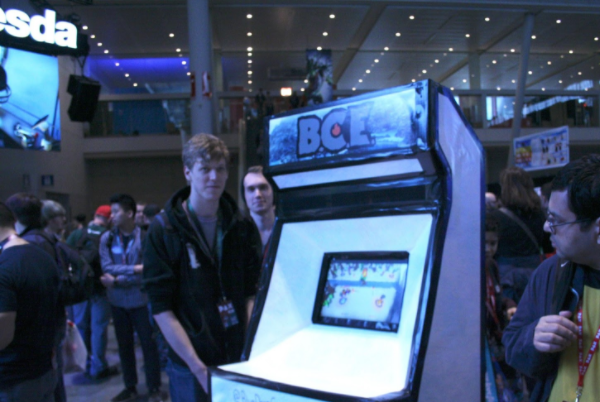 "A white foam board cabinet with a front marquee that reads ""B.C.E"" in stylized font and an inset touch screen surrounded by a few men in hoodies."