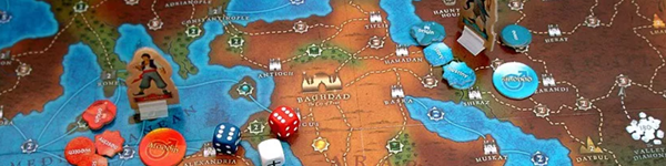 A board game laid out, showing a desert like biome surrounded by water, three dice and cardboard figures above other tokens. This is the play space for the board game Tales of the arabian Nights.