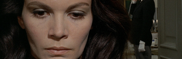 a brunette woman with a stern face and defined chin takes up the left side of the camera. This is a still from the film A Lizard in a Woman's Skin